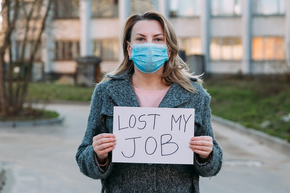"""Woman wearing face mask holds sign saying """"lost my job""""."""