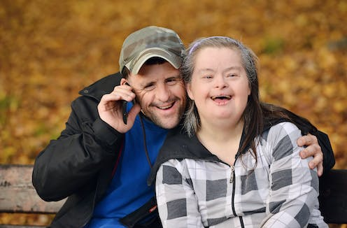 A couple with Down's Syndrome smiles at the camera, golden autumn leaves behind them.