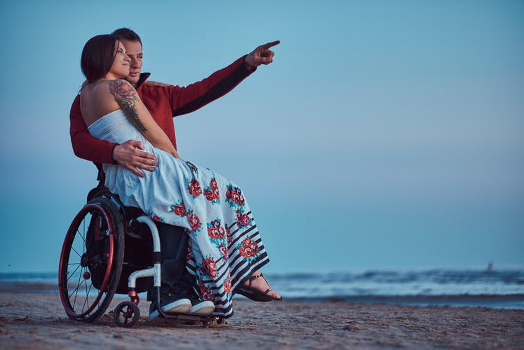 A woman sit on a man's lap as he sits in his wheelchair and points to something in the distance on a beach.