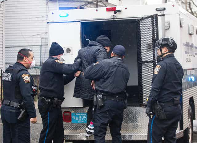 Police help a handcuffed person into the back of a police vehicle.