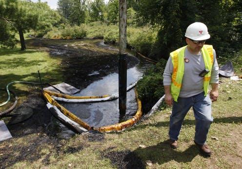 A worker stands on the bank of a creek covered in oil.