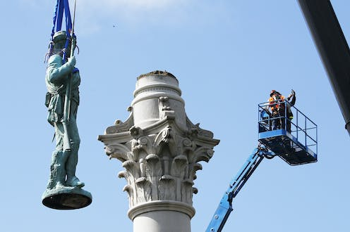 A statue is removed from its pedestal.