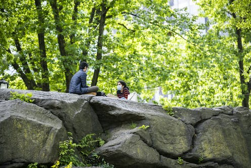 Man and woman wearing masks, sitting on rocks in Central Park, New York, NY