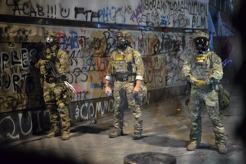 Armed federal officers stand in front of graffiti.