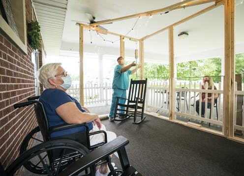 Maintaining social distance, a resident at a Midwest nursing home talks with a visitor.