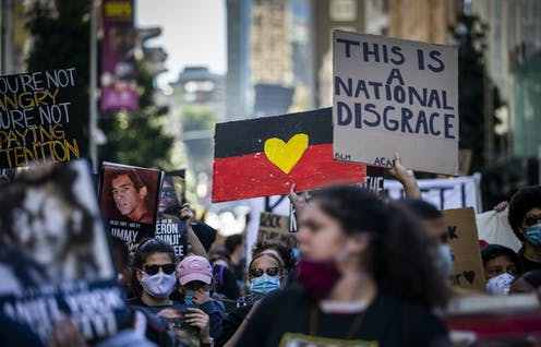 Black Lives Matter rally with sign, 'This is a national disgrace'