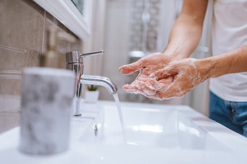 Man's hands lathered with soap at the sink, tap running.