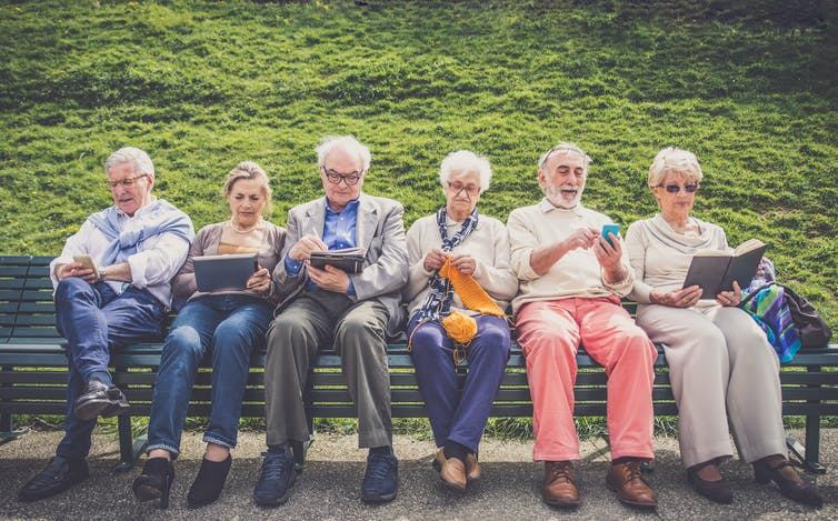 Older people sitting on a park bench, reading, looking at phones