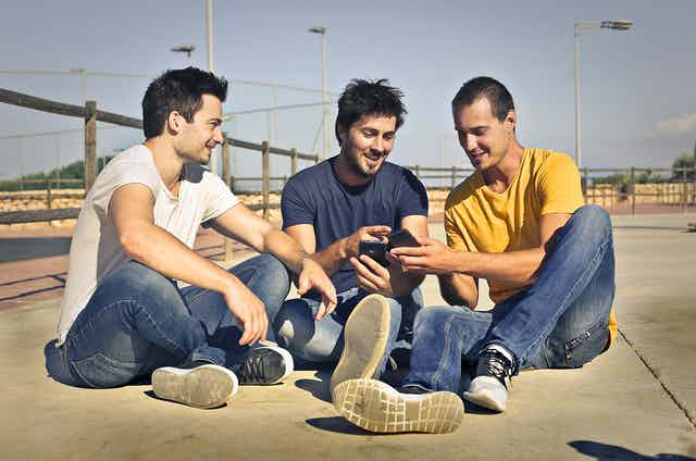 Three young men, smiling and sitting on the ground looking at their mobile phones