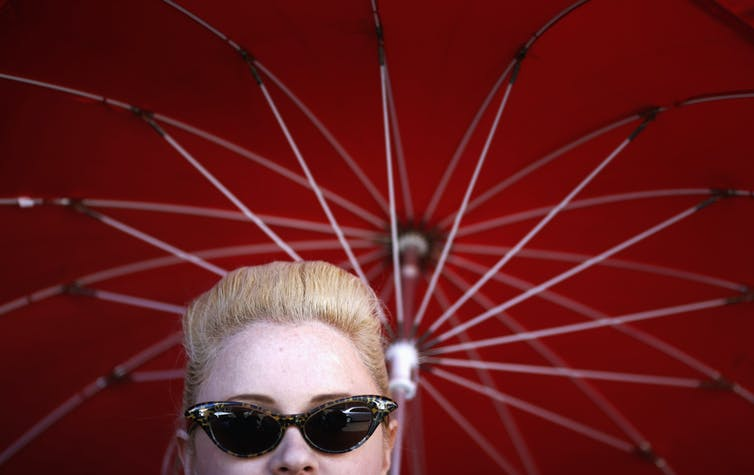 Woman wearing sunglasses under a red umbrella