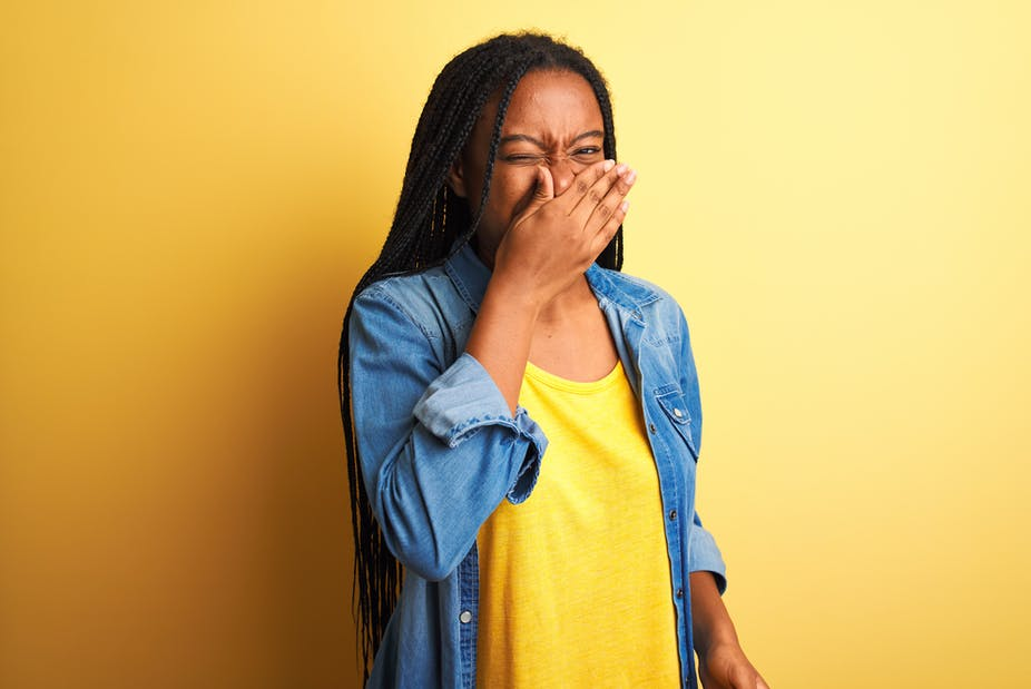 Black woman plugs her nose because of bad smell.
