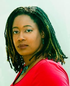 Photograph of author NK Jemisin, a Black woman wearing a red top.