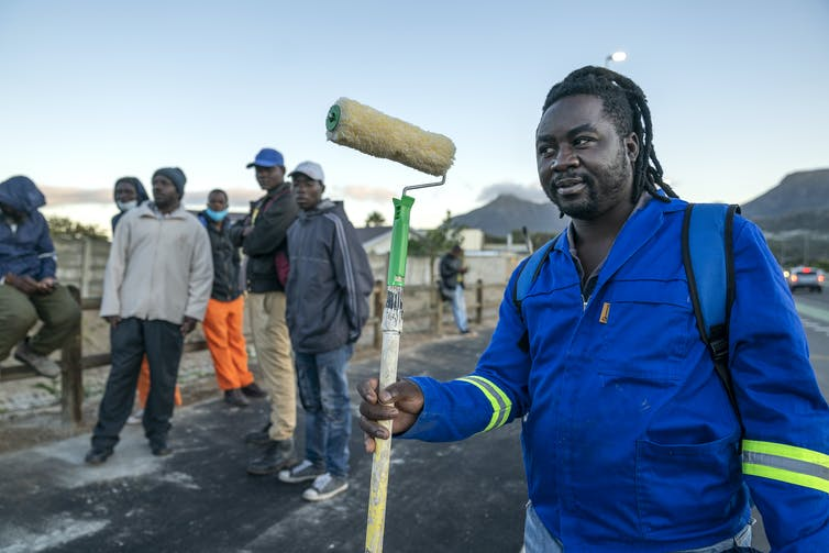 A South African decorator working in the informal sector stands by the roadside waiting for work.