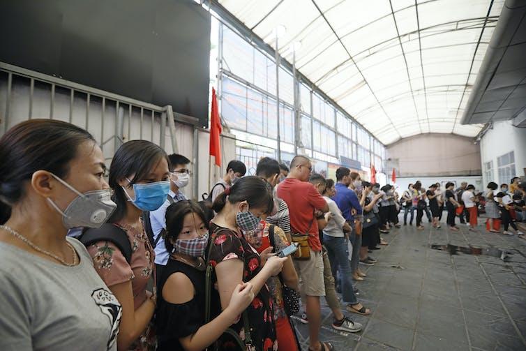 People in Vietnam queue to receive unemployment benefits.