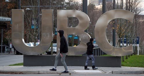 A man on a skateboard and a young woman pass large letters spelling out UBC at the University of British Columbia in Vancouver.