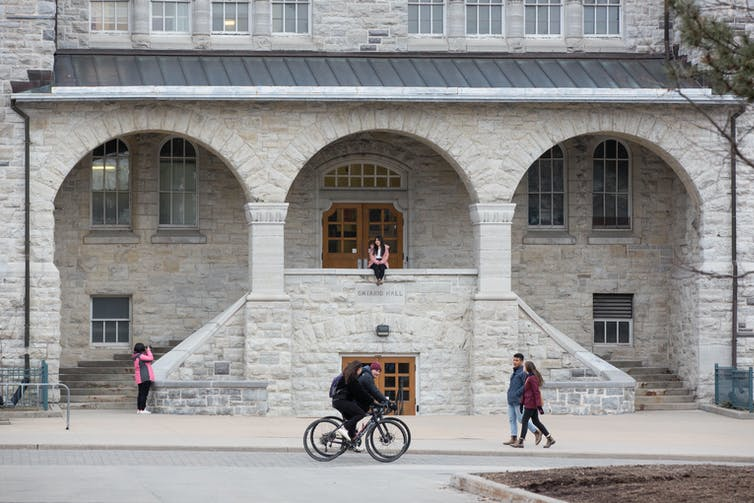 A student on a bicycle and two people pass a stone university building while another student sits on the building's railing.