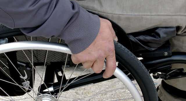 Man's hand on wheel of wheelchair.