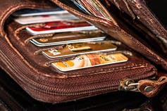 A weathered brown wallet stuffed with credit cards