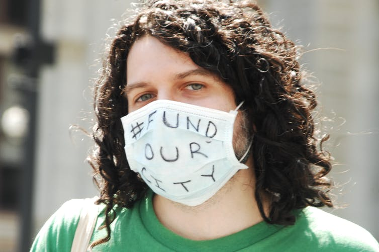 A protestor wearing a mask that says 'Fund our city.'
