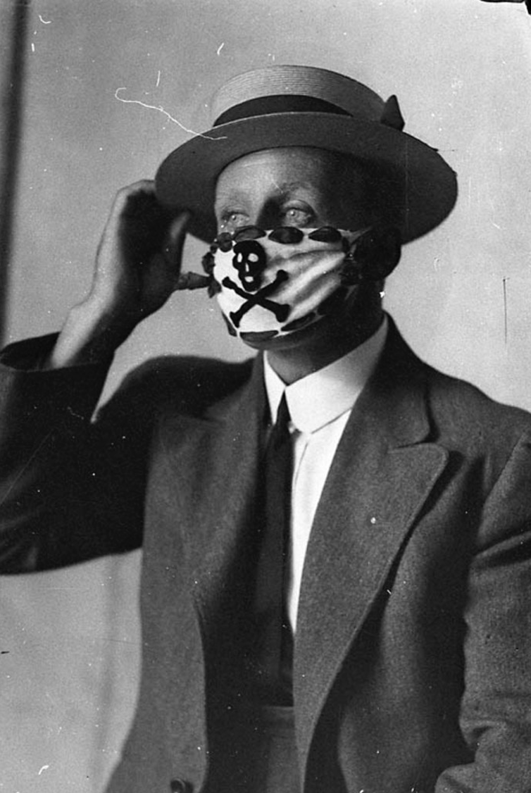 Man wears white face mask with black skull and cross.