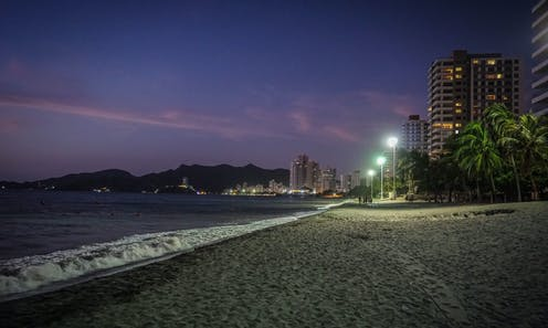 A tropical beach in the evening, with street lamps casting light on the sea.