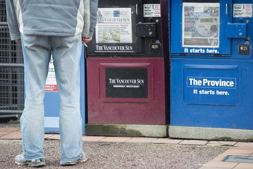A man stands in front of newspaper boxes.