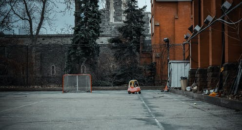 An empty schoolyard, with a hockey goal and toddler car in the background.