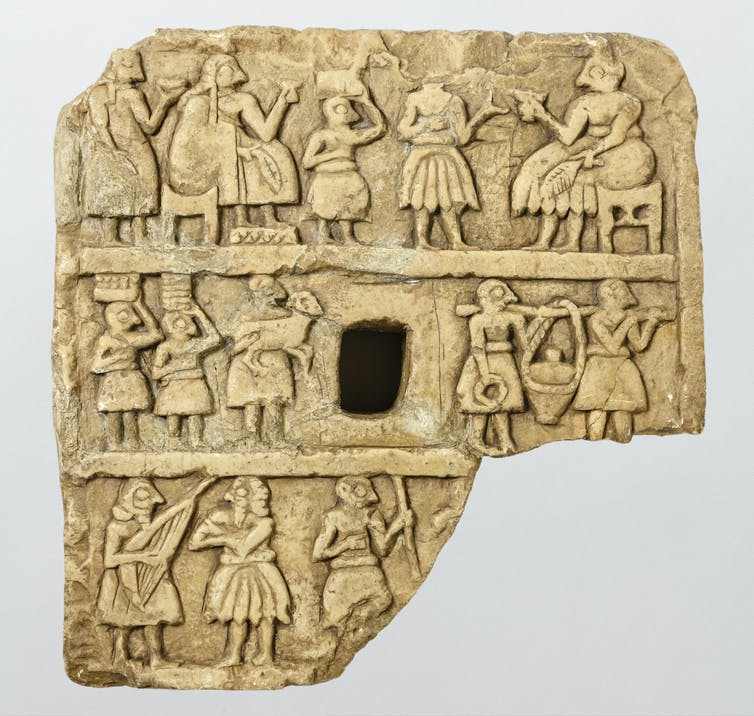 Stone plaque showing people gathered drinking out of cups