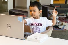A young boy in a Harvard T-shirt examines a laptop with one finger in the air.