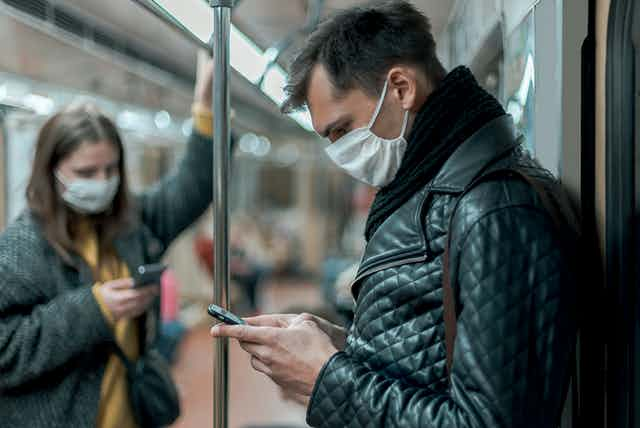 A man in the foreground and a woman in the background stand on a subway train—both are wearing masks and looking at their mobile phones.