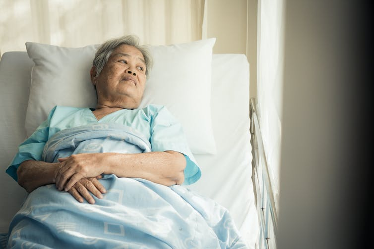 Elderly woman lying in hospital bed.
