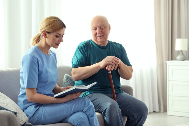 A nurse and a man with a walking stick are seated on a couch. The nurse is reading.