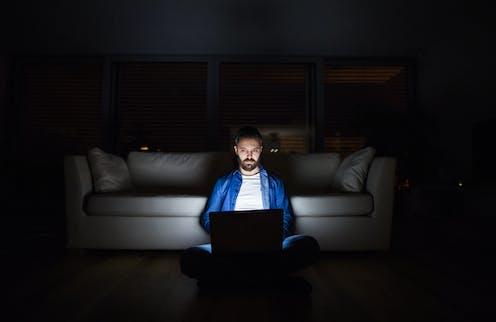 Man using laptop in the dark.
