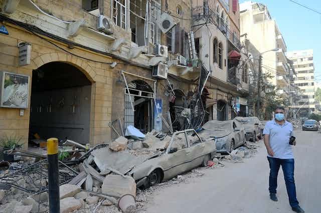 A man walks next to damaged vehicles in the aftermath of a massive explosion in Beirut, Lebanon.