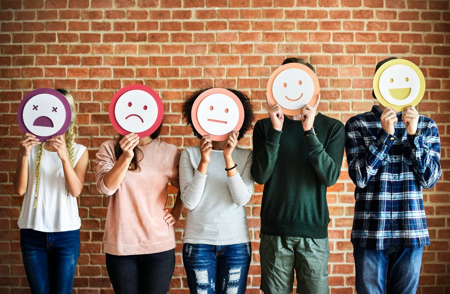 Five people hold up different emotion masks over their faces.
