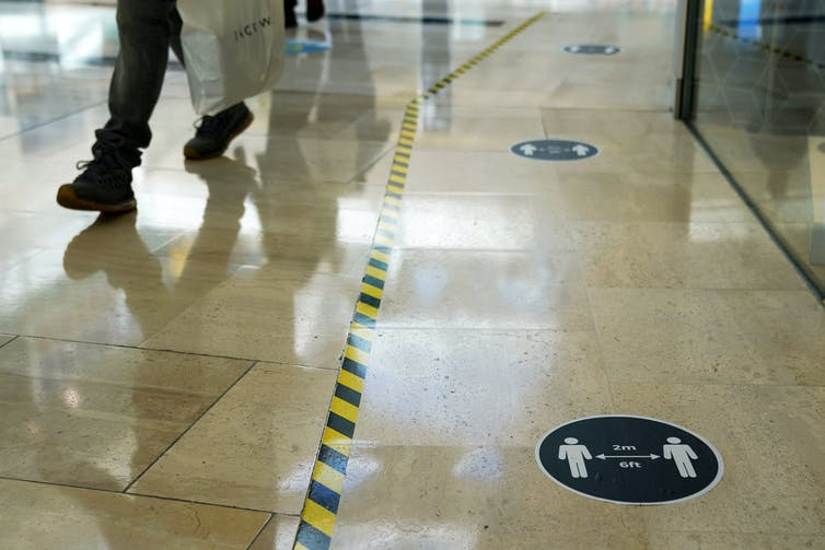 Floor markings indicating where to walk in order to maintain physical distance in a public space.
