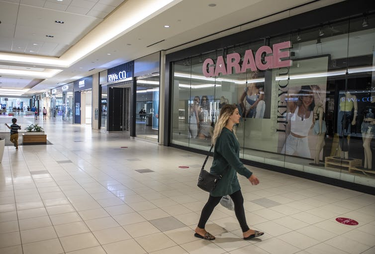 A woman with long blonde hair walks in a relatively empty shopping mall, a darkened Garage store in the background.