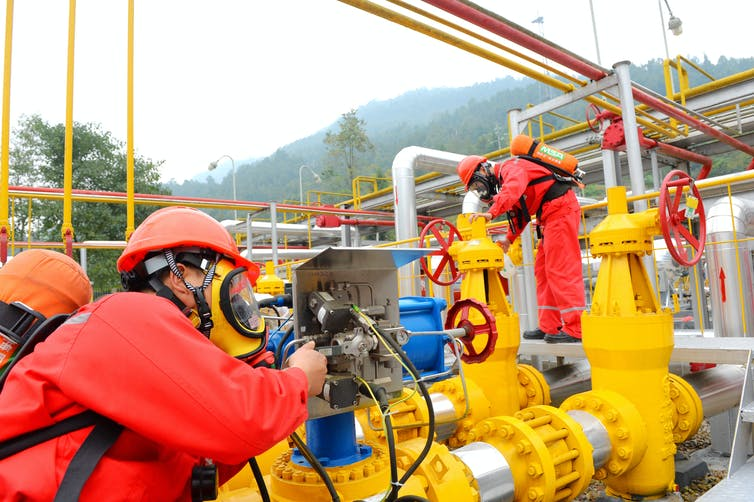 Technicians examine pipes at a shale gas facility in China