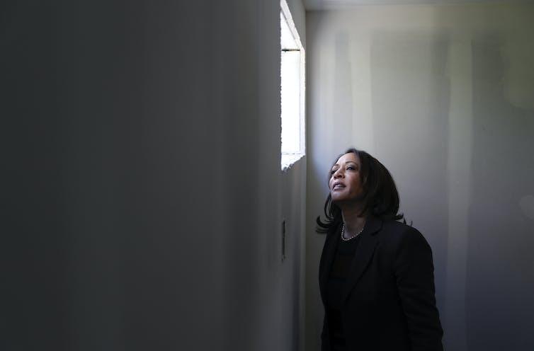 Sen. Kamala Harris peers out of a window at Veterans Village in Las Vegas.