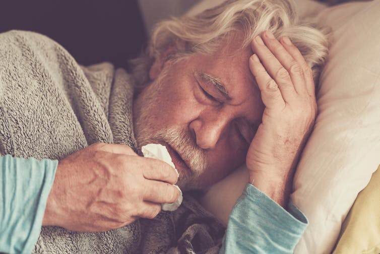 Elderly man in bed with a fever.