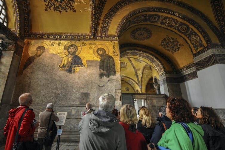 Visitors inside Hagia Sophia in front of Jesus Christ's mosaic