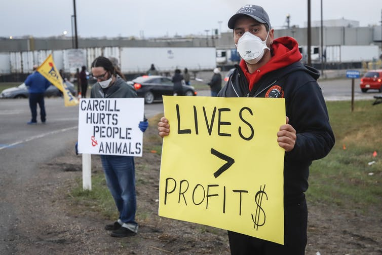 A man wearing a mask carries a sign that says lives are more important than profits outside a Cargill meat-processing plant.