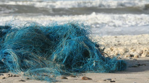 A blue fishing net washed up on the beach
