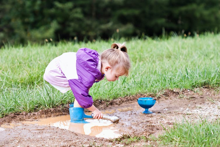 A young girl plays in the mud.