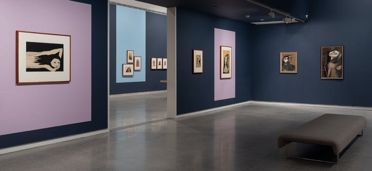 Empty gallery space with paintings on walls