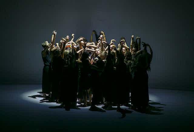 A group of dancers reach upwards.