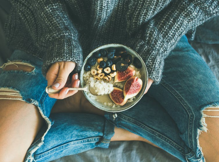 Woman holds healthy breakfast bowl with blueberries, guava and cereal.