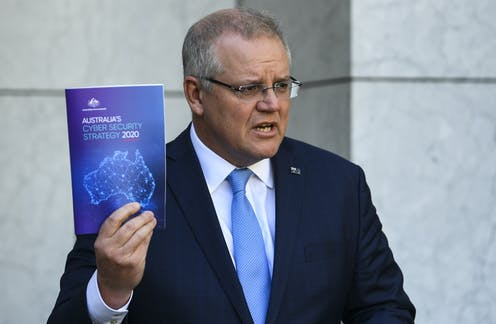 Australian Prime Minister Scott Morrison holds up a copy of Australia's Cyber Security Strategy 2020
