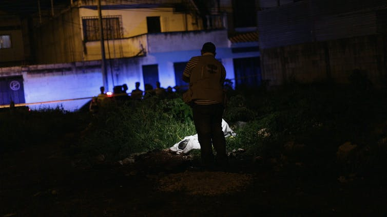 Man photographs dead body at nighttime.