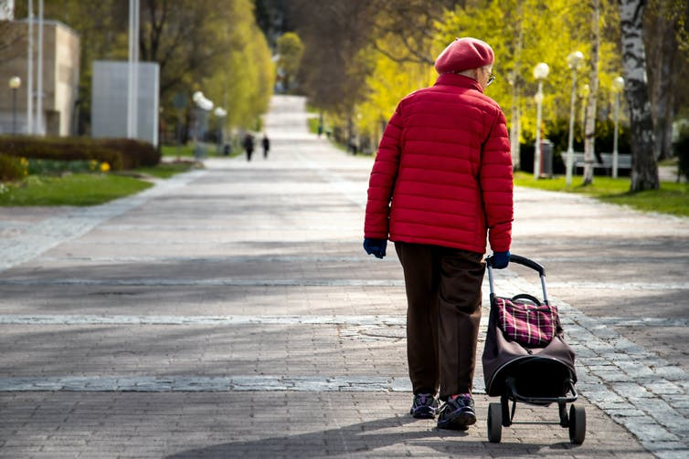 Older woman walking with rolling shopping bag.
